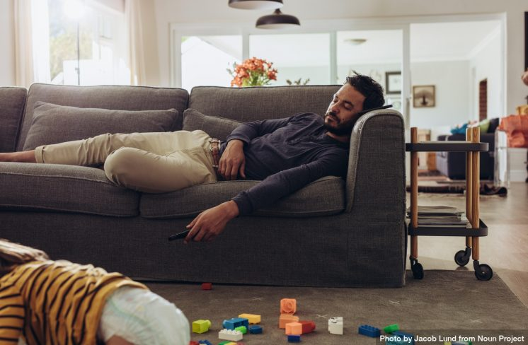 Far i sofaen, mens barn leger på gulvet. Foto: Jacob Lund, Noun Project