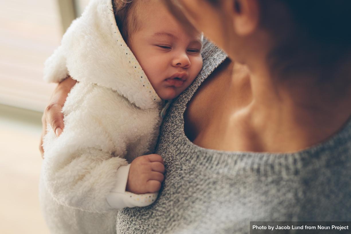 Baby sover på mors arm. Foto: Jacob Lund, Noun Project
