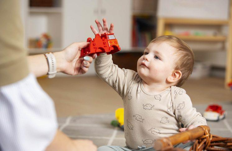 Dreng rækker ud efter legetøj. Foto: Rie Neuchs