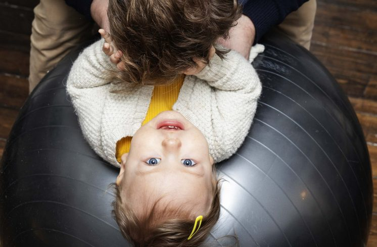 Pige ligger på bold med far. Foto: Rie Neuchs