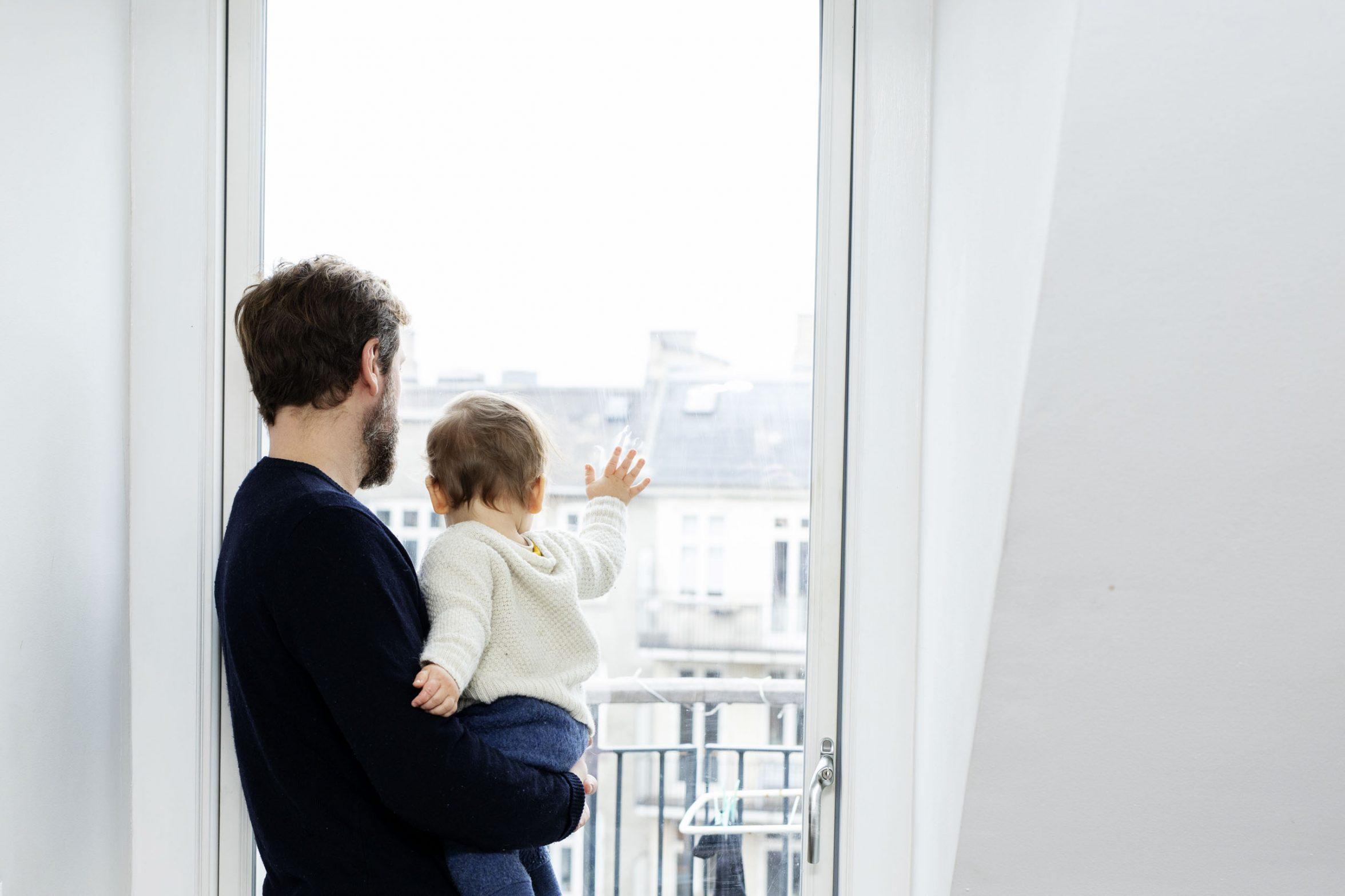 Far og barn kigger ud af vinduet. Foto: Rie Neuchs