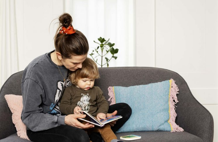 Mor sidder i sofa og læser for dreng. Foto: Rie Neuchs