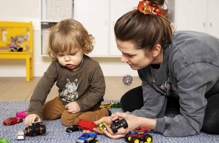 Mor og dreng leger med biler på gulvet. Foto: Rie Neuchs