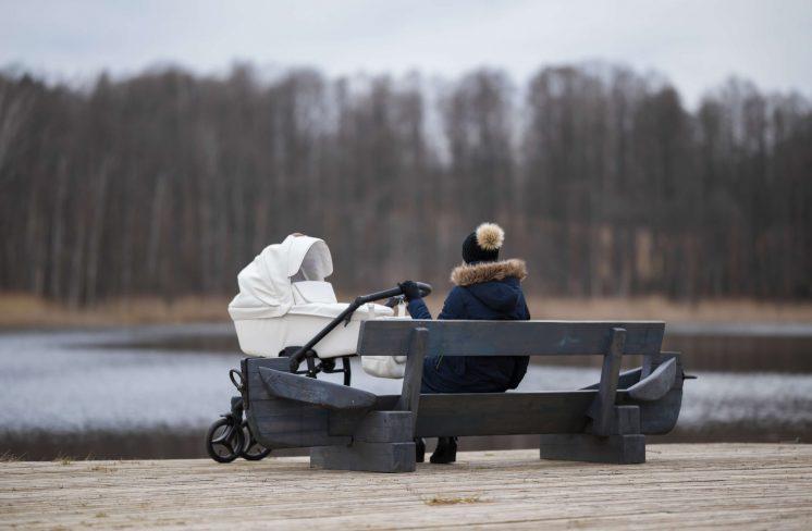 Mor med barnevogn sidder alene på en bænk. Foto: Shutterstock